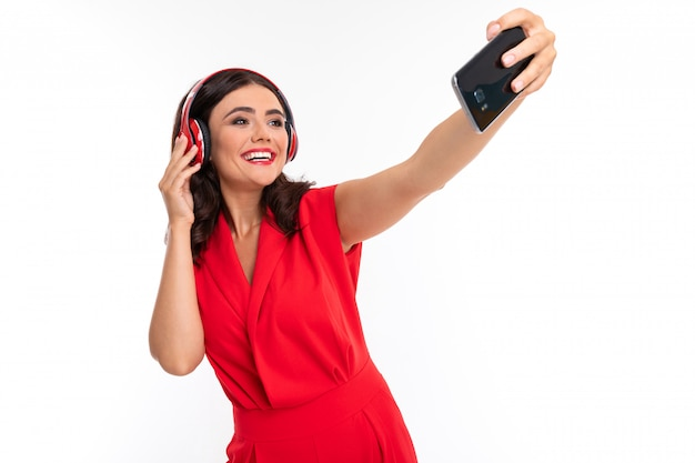 Een jonge vrouw met rode lippen luistert naar muziek in een koptelefoon, doet selfie en glimlacht