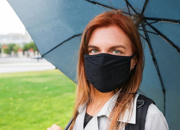 Een jonge vrouw met rood haar onder een blauwe paraplu met een zwart beschermend masker