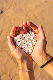 Een jonge vrouw met stenen in haar hand op popcorn beach bij de stad corralejo, ten noorden van het eiland fuerteventura, canarische eilanden. spanje
