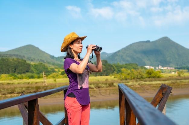 Een jonge vrouw met verrekijker vanaf de houten pieren van de urdaibai-moerassen, een biosfeerreservaat in bizkaia naast mundaka. baskenland
