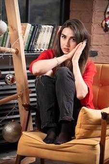 Een jonge vrouw model in rode blouse zitten en poseren.
