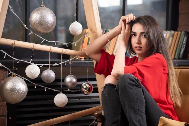 Een jonge vrouw model in rode blouse zitten en poseren. Gratis Foto