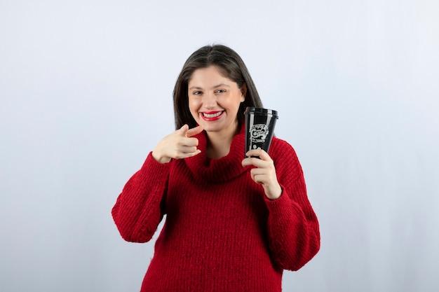 Een jonge vrouw model in rode trui met een kopje koffie wijzend op camera