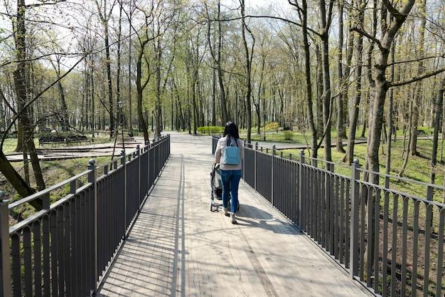 Een jonge vrouw, moeder met een kinderwagen op een lentewandeling gaat over de brug in het park. achteraanzicht.