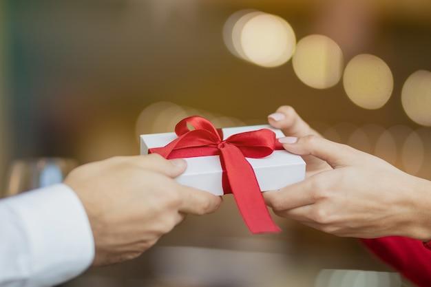 Een jonge vrouw neemt een cadeautje van haar vriend. warme en mooie onscherpe achtergrond van een restaurant. twee glazen wijn en een roos op de tafel van het café. valentijnsdag concept.