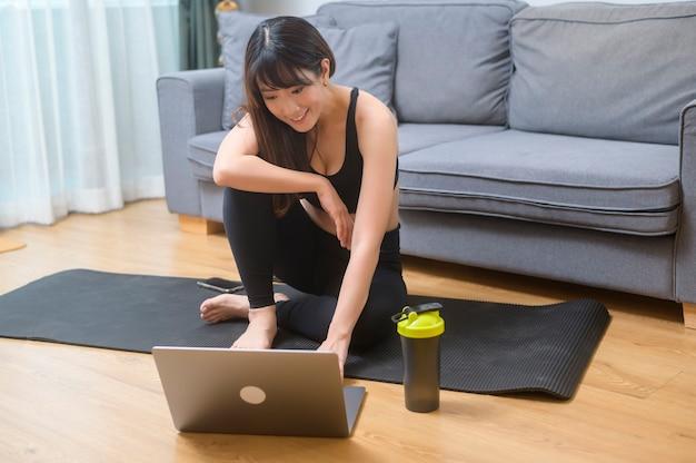 Een jonge vrouw oefent en kijkt naar online fitnesstraining op de laptop in de woonkamer thuis, sport, fitness en technologieconcept.