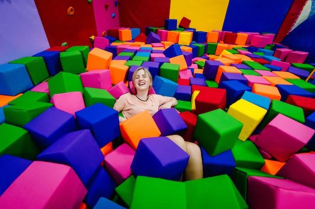 Een jonge vrouw of meisje, moeder spelen en springen in zachte kubussen in het droge zwembad van de kinderkamer van het spel voor verjaardag. uitgaanscentrum. binnenspeeltuin in schuimrubberen bak in trampoline.