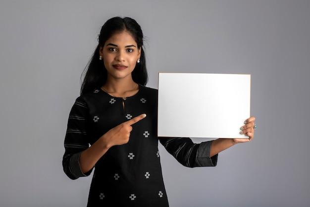 Een jonge vrouw of zakenvrouw met een bord in haar handen op een grijze achtergrond.