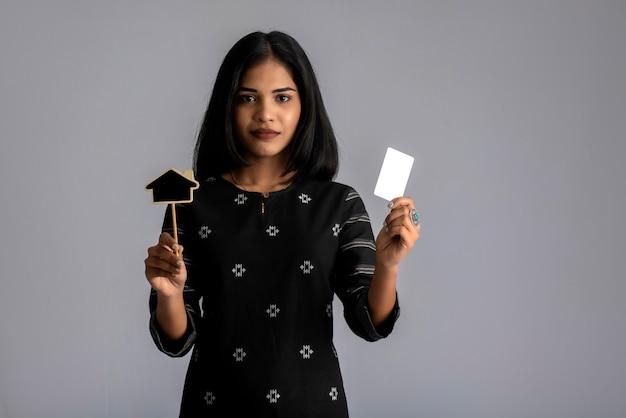 Een jonge vrouw of zakenvrouw met een klein bordje en een creditcard in haar handen op een grijze muur.