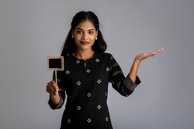 Een jonge vrouw of zakenvrouw met een klein uitgesneden bord in haar handen op een grijze muur.
