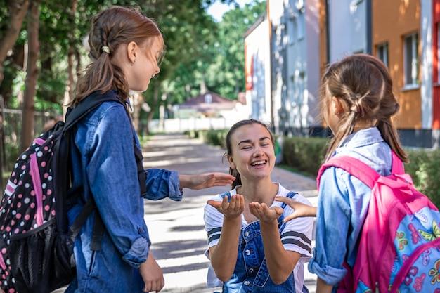 Een jonge vrouw ondersteunt de dochters moreel, hand in hand, moedigt de kinderen aan en begeleidt de leerlingen naar school.