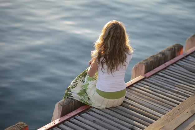 Een jonge vrouw ontspant op het strand bij de pier