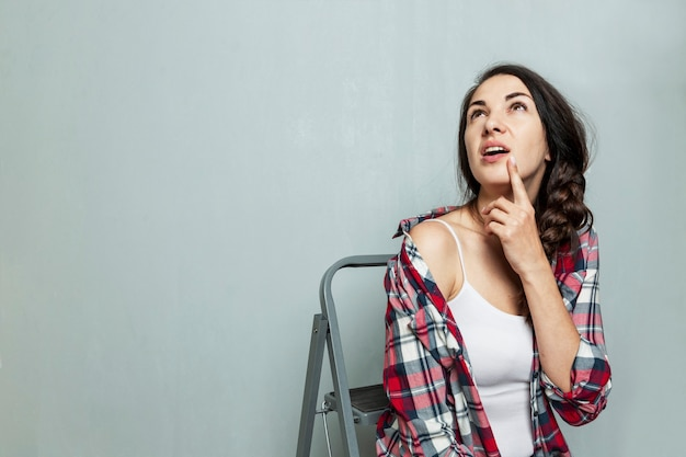 Een jonge vrouw op de achtergrond van een geschilderde muur zit op een trapladder. mooie brunette met een vlecht. bouw en reparatie. ruimte voor tekst.