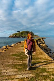 Een jonge vrouw op de catwalk om bij eb naar het eiland san nicolas te gaan vanaf het strand van isuntza in lekeitio, baskenland