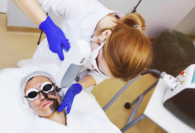 Een jonge vrouw op de procedure van koolstofschillen op de achtergrond van moderne kosmetiekruimte.