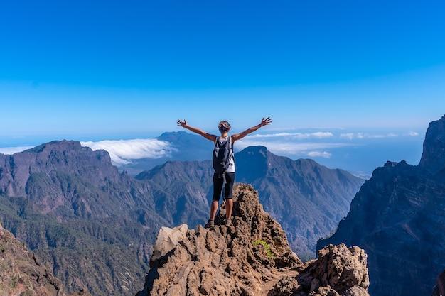 Een jonge vrouw op de top van de vulkaan caldera de taburiente bij roque de los muchachos op een zomermiddag met open armen, la palma, canarische eilanden. spanje