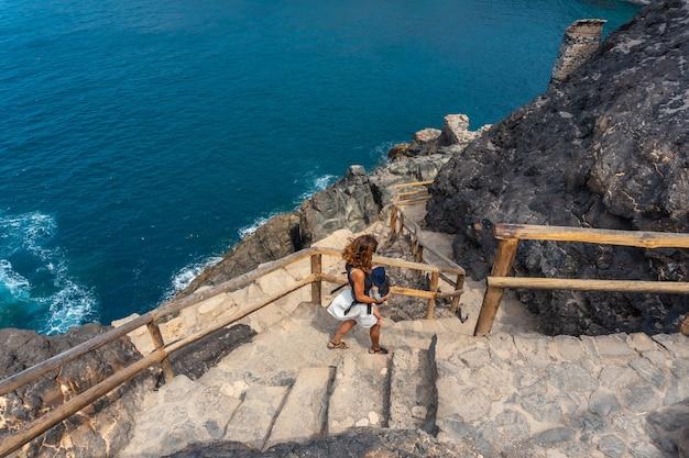 Een jonge vrouw op de trappen van het pad naar de grotten van ajuy, pajara, westkust van het eiland fuerteventura, canarische eilanden. spanje