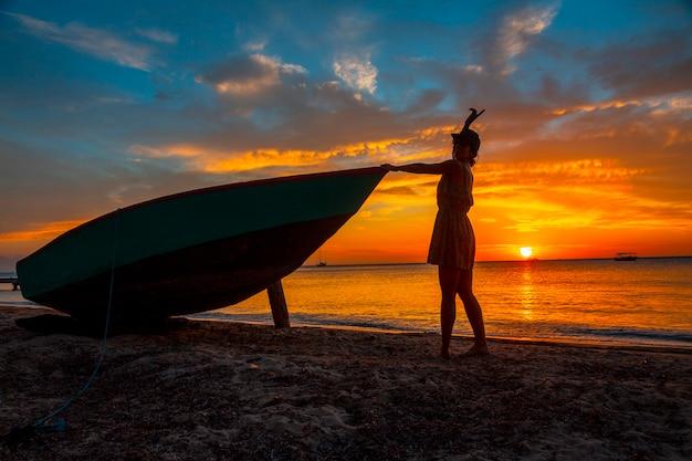 Een jonge vrouw op het strand in een boot bij roatan sunset from west end. honduras