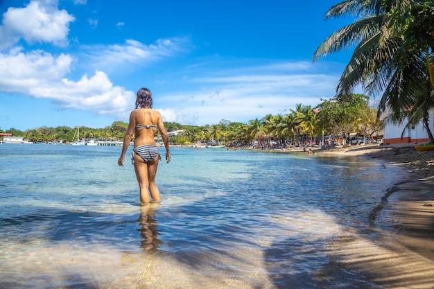Een jonge vrouw op zoek naar zee op west end beach op roatan island. honduras