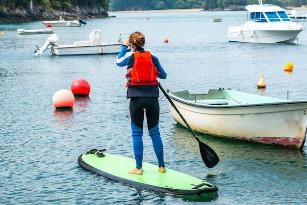 Een jonge vrouw peddelt aan het surfen in de zee in urdaibai, een biosfeerreservaat in bizkaia naast mundaka. baskenland