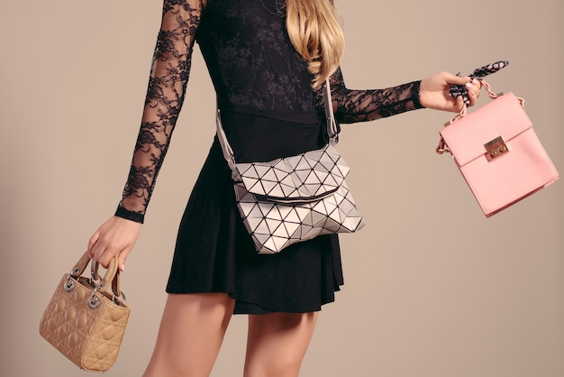 Een jonge vrouw poseren in een zwarte jurk en handtassen