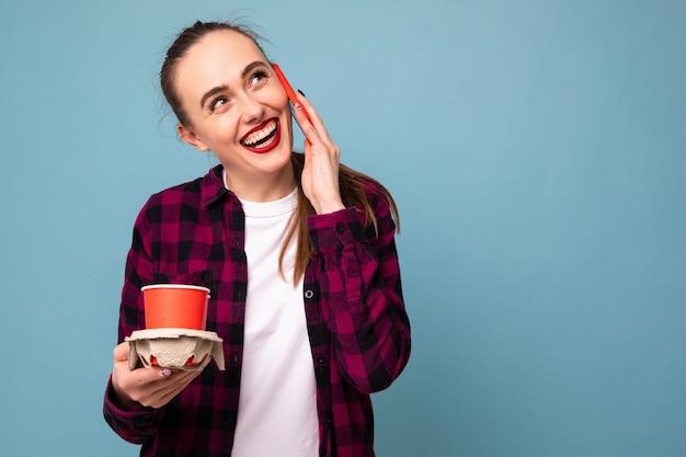 Een jonge vrouw praat aan de telefoon en houdt twee koffie in papieren bekertjes