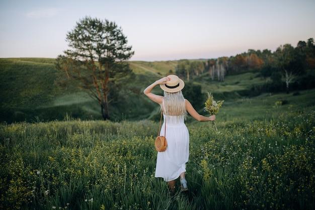 Een jonge vrouw rent over een veld met een hoed in de ene hand en wilde bloemen in de andere.