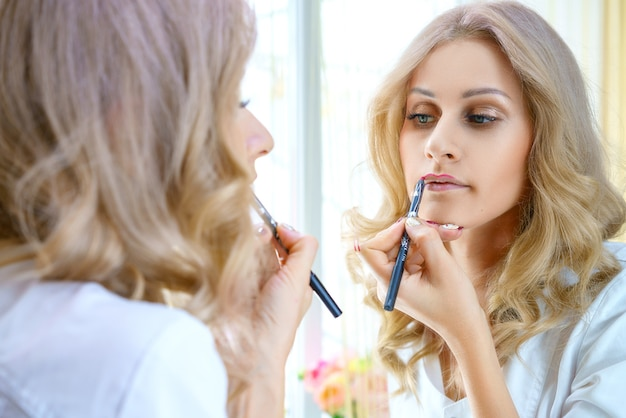 Een jonge vrouw schildert haar lippen in de spiegel.