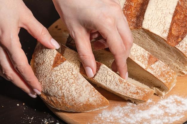 Een jonge vrouw sneed vers gebakken brood in plakjes. gezond eten.
