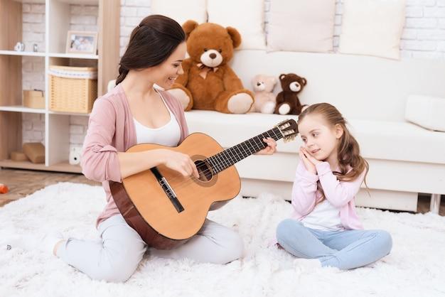 Een jonge vrouw speelt gitaar en een meisje zingt.
