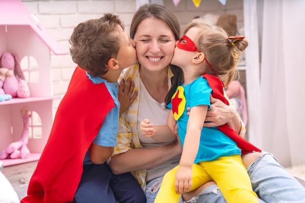Een jonge vrouw speelt met haar kinderen in superhelden