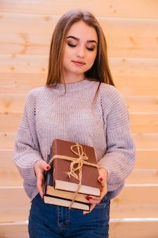 Een jonge vrouw staat en heeft een stapel boeken in haar handen. boeken gebonden met een touwtje. het meisje is een student, die zich voorbereidt op de universiteit of een examen.