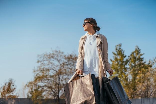 Een jonge vrouw staat in een auto met tassen in haar handen