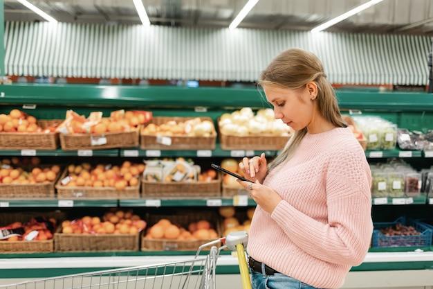 Een jonge vrouw staat in een kruidenierswinkel en leest berichten op haar mobiele telefoon.