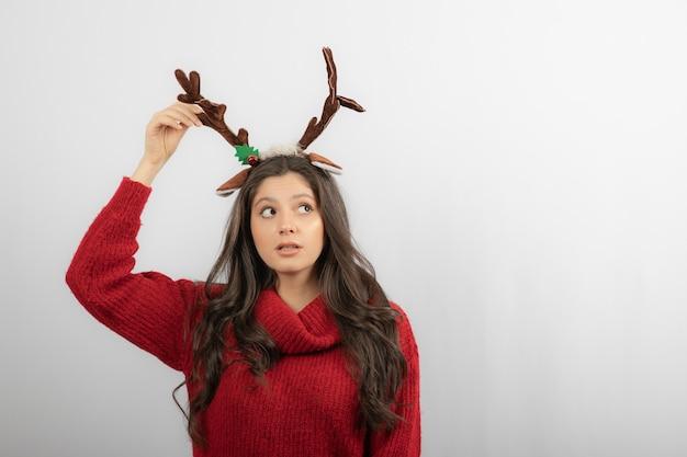 Een jonge vrouw staat met een hoofdband in de vorm van kersthoorns.