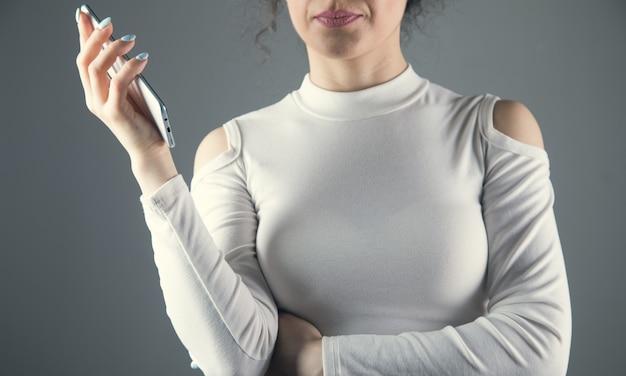 Een jonge vrouw staat met een telefoon in haar hand op een grijze scène