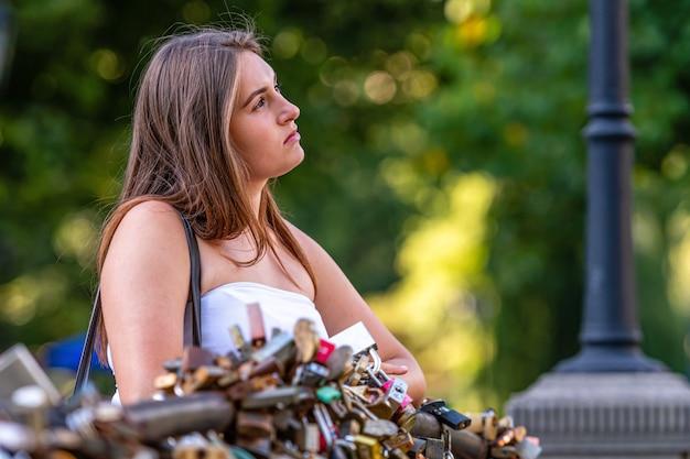 Een jonge vrouw staat op een brug met liefdessloten en staart dromerig in de verte, onscherpe natuurlijke achtergrond