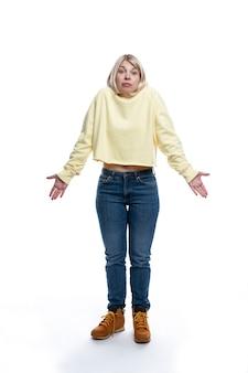 Een jonge vrouw staat op en gooit verrast haar handen in de lucht. blonde in een gele trui en jeans. volledige hoogte. geïsoleerd op een witte achtergrond. verticaal.