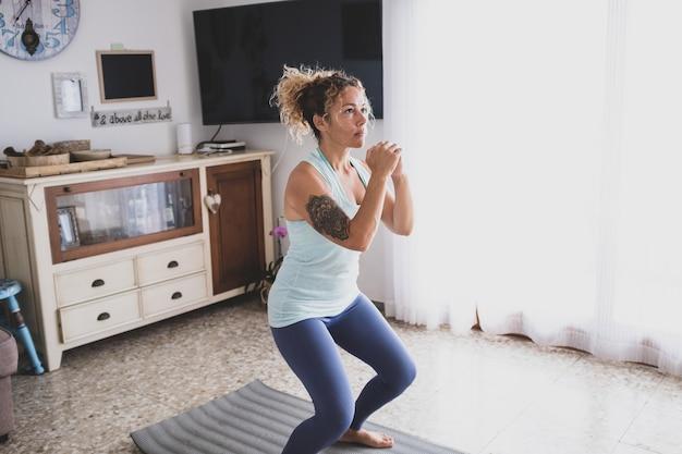 Een jonge vrouw thuis doet alleen oefeningen om fit en gezond te zijn - krullend meisje doet yoga in haar huis in quarantaine en lockdown - mooie actieve vrouw die plezier heeft