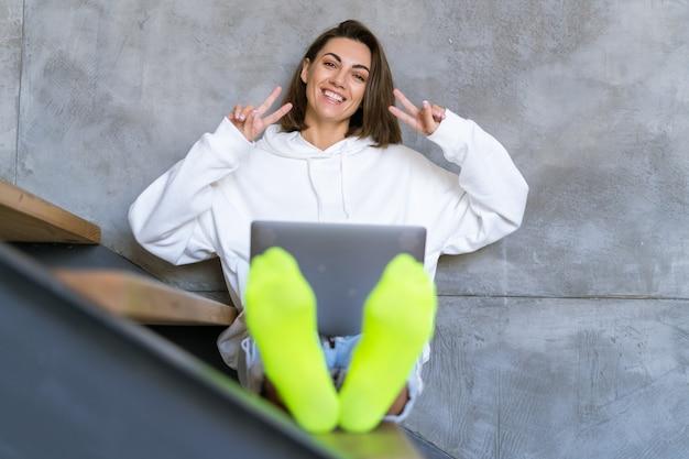 Een jonge vrouw thuis in een witte hoodie en spijkerbroek zit op de trap met een laptop op haar knieën