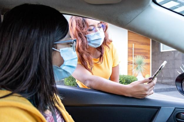 Een jonge vrouw toont haar mobiele telefoon aan de bestuurder van een auto, beiden met gezichtsmaskers
