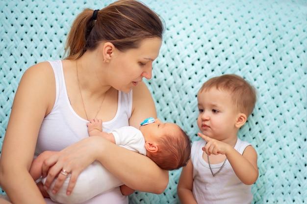 Een jonge vrouw toont haar oudste zoon zijn jongere pasgeboren broer