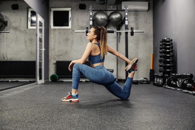 Een jonge vrouw traint in de sportschool. fit lachende vrouw in sportkleding en een goede fysieke vorm strekt zich uit over de beenspieren in de sportschool. ze deed een stap naar voren en hield haar been met één hand vast