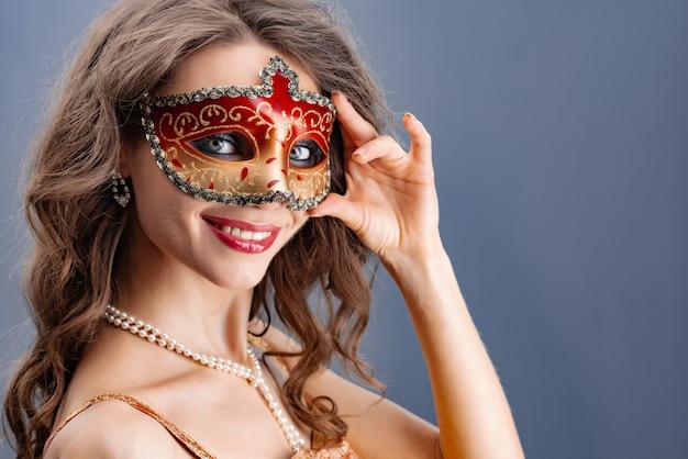 Een jonge vrouw trekt een carnavalsmasker aan