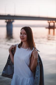 Een jonge vrouw trekt een spijkerjasje aan op een koele zomeravond bij zonsondergang bij de brug over de rivier
