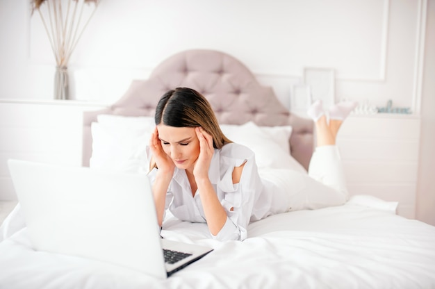 Een jonge vrouw van 25 jaar europees uiterlijk ligt op een bed met een laptop thuis op een wit bed. voelt een ongezonde hoofdpijn of vermoeide ogen, slecht nieuws