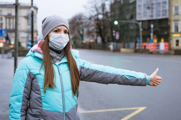 Een jonge vrouw van blanke etniciteit in een warme jas en muts staat op straat met een masker stopt t...