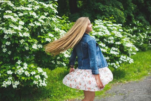 Een jonge vrouw van europees uiterlijk met lang blond haar, gekleed in een korte jurk, staat tegen de achtergrond van witbloeiende struiken. zonnige lentedag. natuurlijke vrouwelijke schoonheid