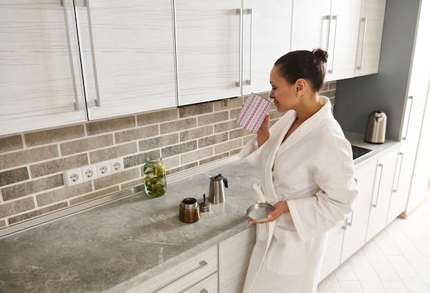 Een jonge vrouw van gemengd ras in een wit wafelgewaad staat in de keuken en geniet van de geur van koffie in een pot in haar hand. ochtendroutine concepten