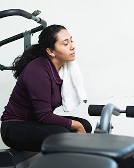 Een jonge vrouw veegt het zweet van haar nek met een handdoek tijdens een pauze in de sportschool